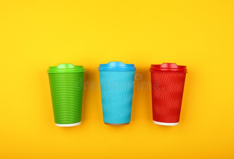 Tres tazas de café de papel coloridas sobre amarillo imagen de archivo libre de regalías