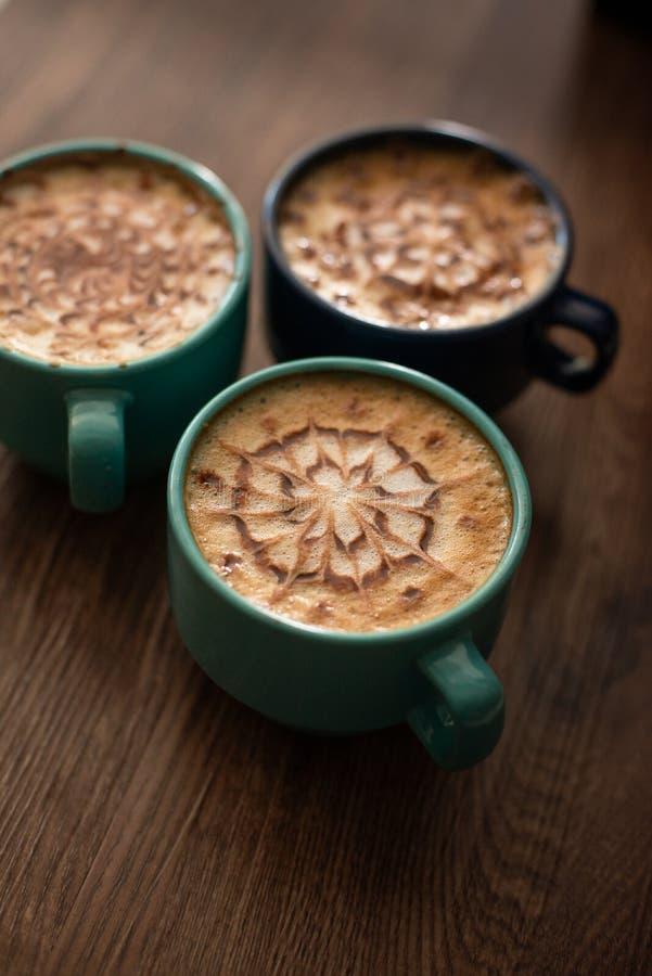 Tres tazas de café que esperan en la tabla fotografía de archivo