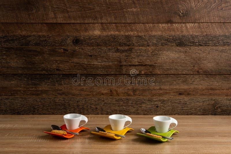 Tres tazas de café vacías con la galleta y la cucharilla cerca imagen de archivo