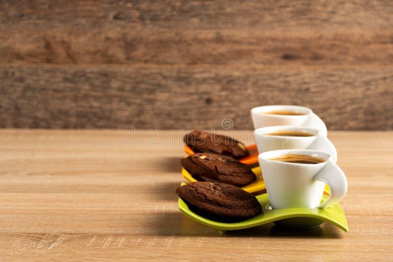 Tres tazas de galletas frescas del café y del chocolate colocadas en la tabla fotos de archivo libres de regalías