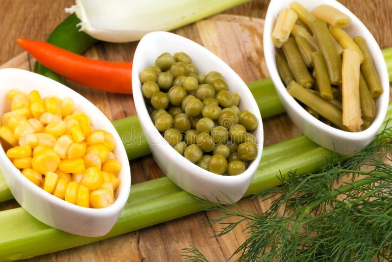 Tres tazas de maíz, de guisantes verdes y de habas imágenes de archivo libres de regalías
