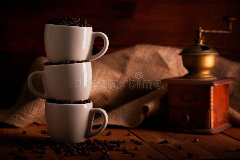 Tres tazas llenas de granos de café en la tabla de madera foto de archivo