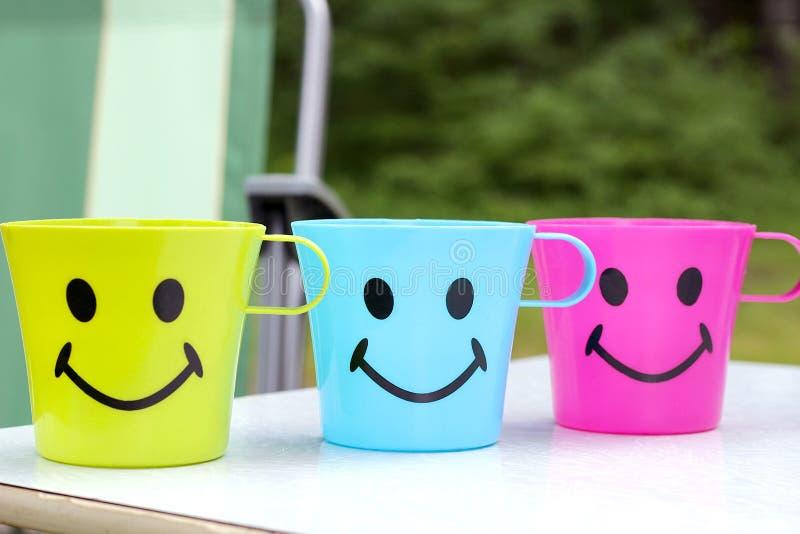 Tres tazas plásticas con una cara atractiva con una sonrisa se están colocando en una mesa de picnic en naturaleza foto de archivo libre de regalías