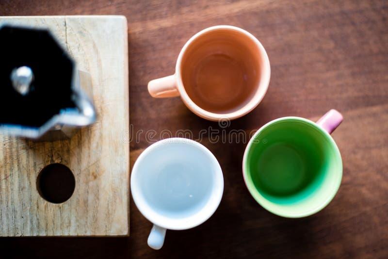 Tres tazas vacías cerca de un moka por completo del café foto de archivo libre de regalías