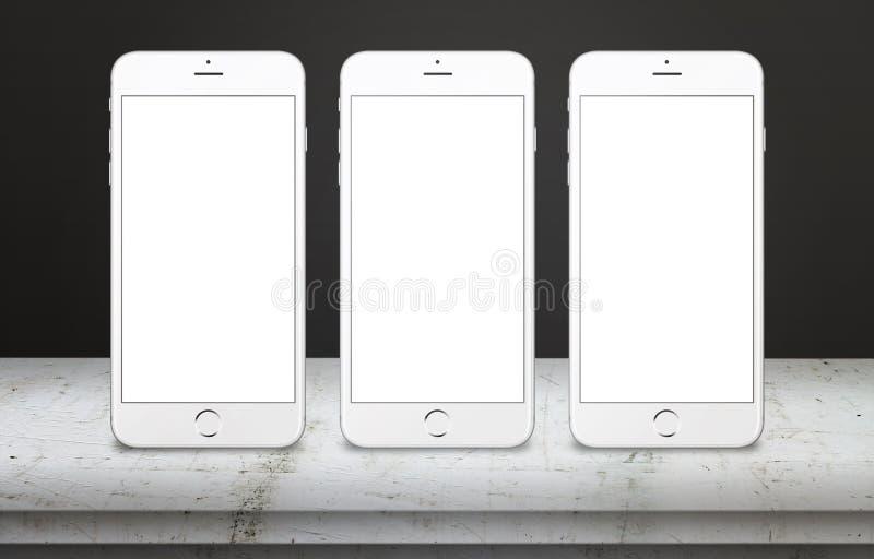 Tres teléfonos móviles blancos en la tabla con la pantalla de visualización en blanco, blanca, aislada para la maqueta ilustración del vector