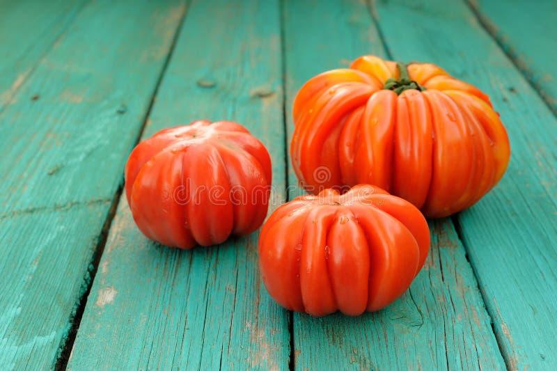 Tres tomates orgánicos frescos de la herencia en la turquesa de madera lamentable foto de archivo libre de regalías