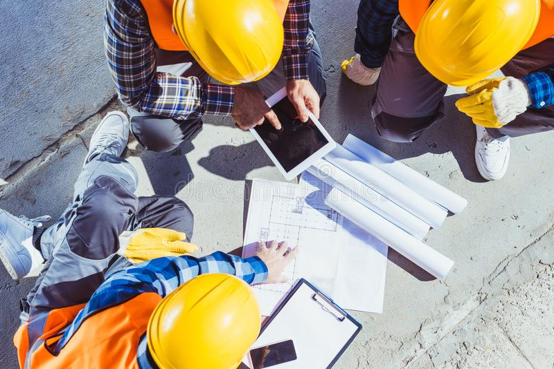 Tres trabajadores de construcción que se sientan en concreto y la discusión fotografía de archivo