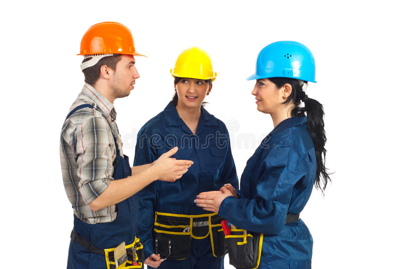 Tres trabajadores del constructor que tienen conversación imagen de archivo