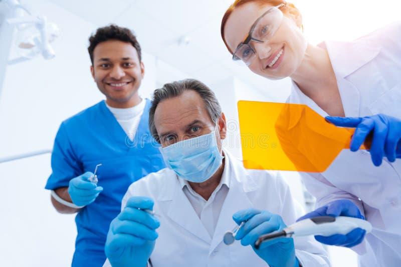 Tres trabajadores médicos que guardan sonrisa en sus caras foto de archivo