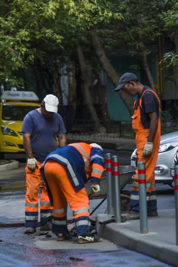 Tres trabajadores martillaron columnas cerca de la acera imagen de archivo libre de regalías