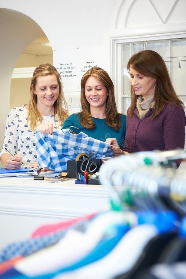 Tres trabajadores voluntarios de sexo femenino en tienda de la caridad fotos de archivo