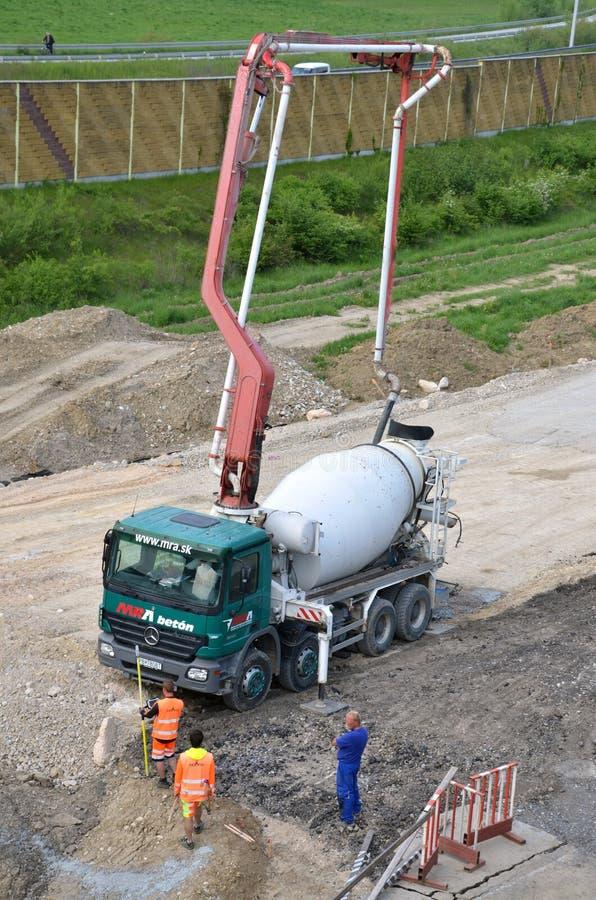 Tres trabajadores y camión concreto del transporte con la bomba concreta de manera operacional Esta actividad se relaciona con la fotografía de archivo libre de regalías