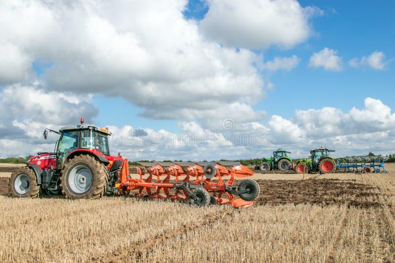 Tres tractores modernos que tiran de arados foto de archivo