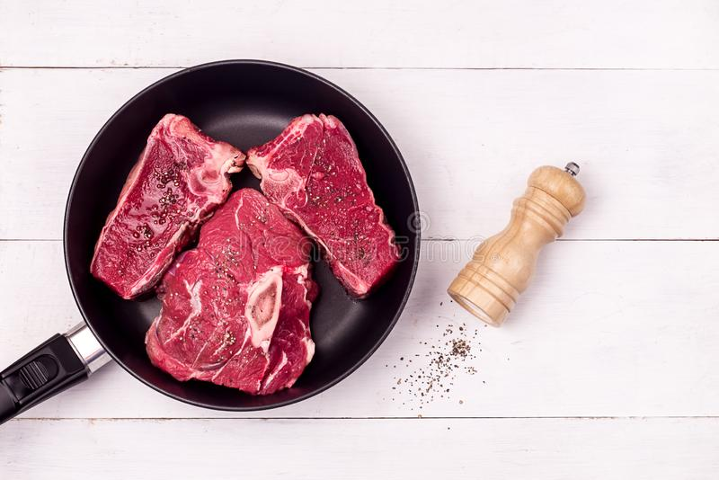 Tres trozos de carne de ternera fresca cruda en el fondo de madera blanca Pan Fondo de Madera Blanca Vista en la parte superior Co imagen de archivo libre de regalías