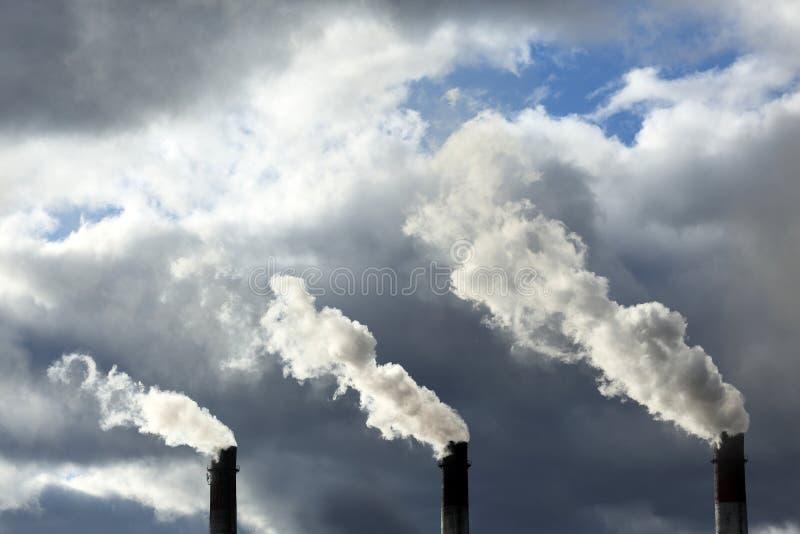 Tres tubos con humo contra la perspectiva de un cielo hermoso imagen de archivo