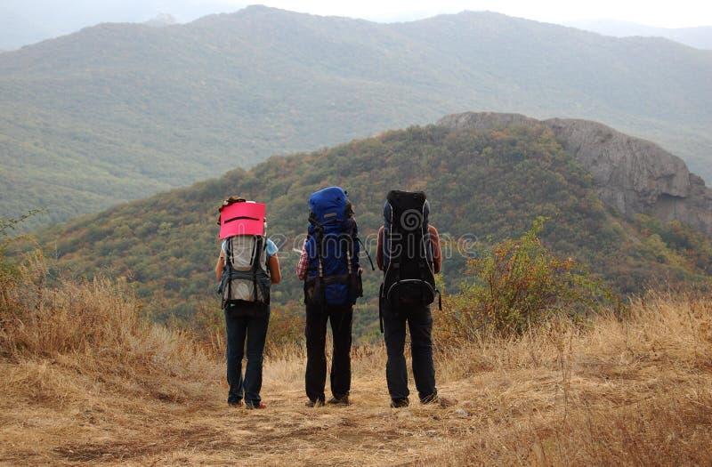 Tres turistas con las mochilas se colocan en una cuesta de montaña fotografía de archivo