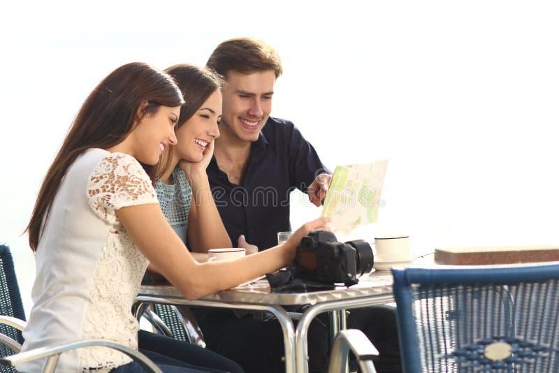 Tres turistas que comprueban la guía en una cafetería fotos de archivo