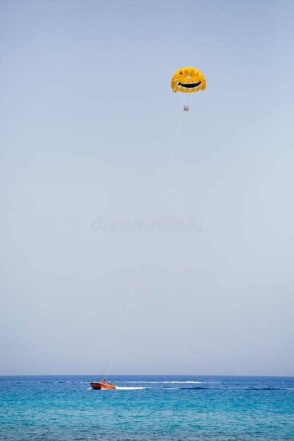Tres turistas que vuelan en un paracaídas amarillo con la cara sonriente en ella foto de archivo