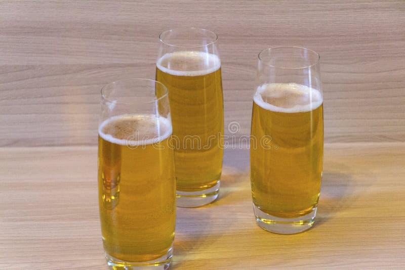 Tres vasos de cerveza en la tabla imagen de archivo