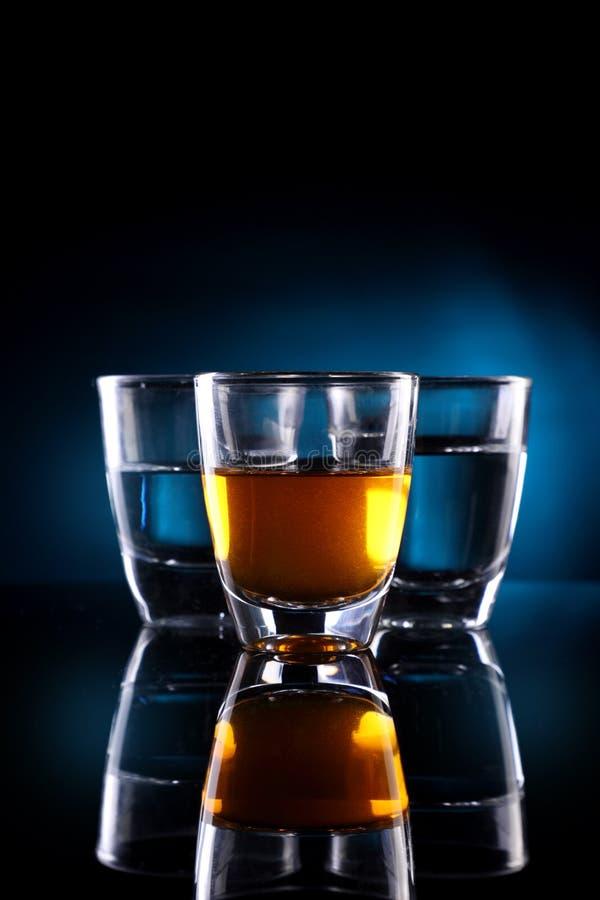 Tres vasos de medida con las bebidas del alcohol foto de archivo