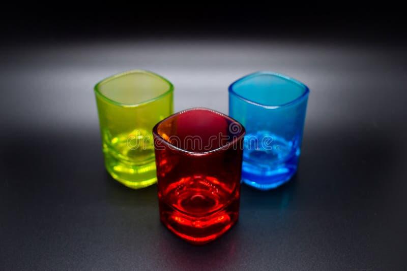 Tres vasos de medida multicolores en fondo negro fotos de archivo