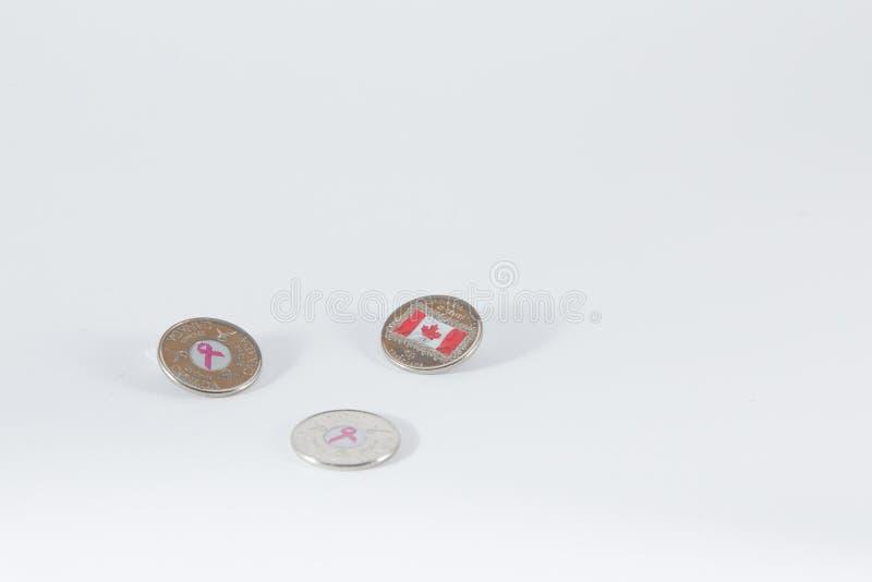 Tres veinticinco monedas canadienses del centavo con símbolos en centro pueden imágenes de archivo libres de regalías