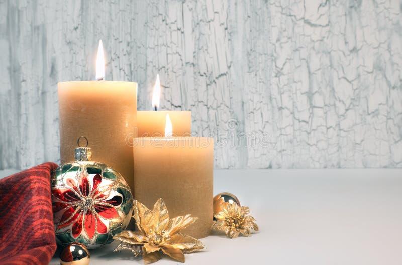 Tres velas ardientes con las decoraciones de oro de la Navidad en fondo neutral rústico fotos de archivo libres de regalías