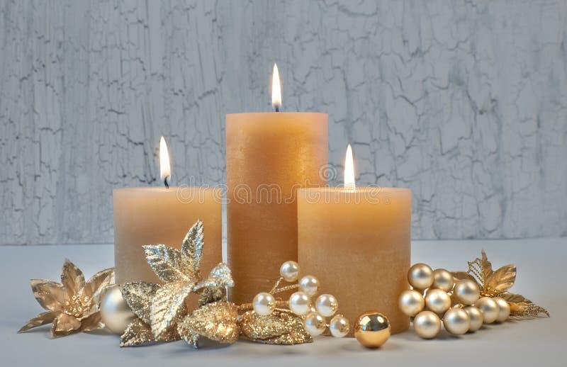 Tres velas ardientes con las decoraciones de oro de la Navidad en rusti imagen de archivo