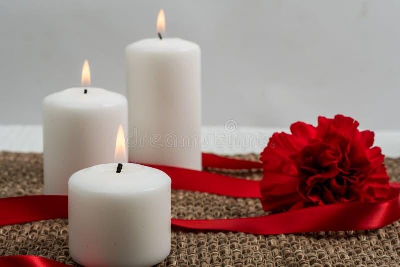 Tres velas con la cinta y el clavel imagen de archivo