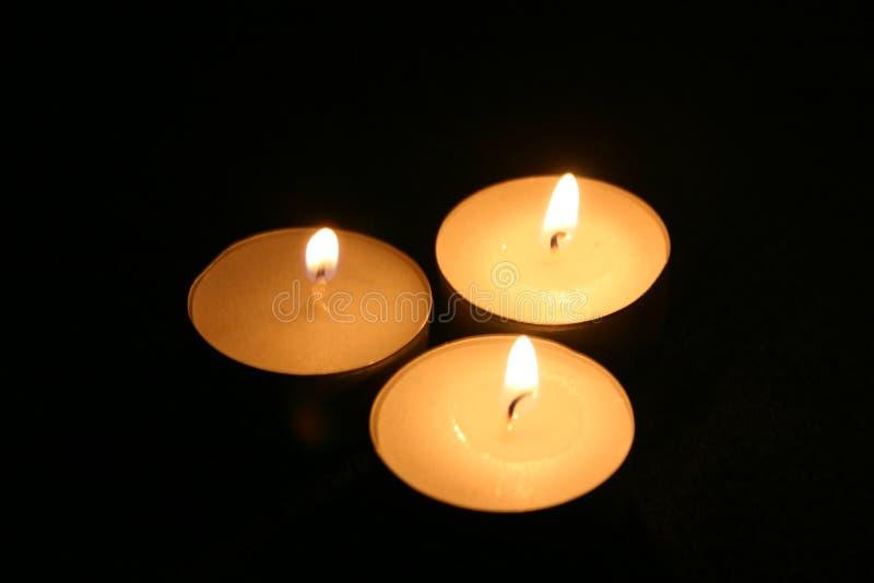 Tres velas en la obscuridad foto de archivo libre de regalías