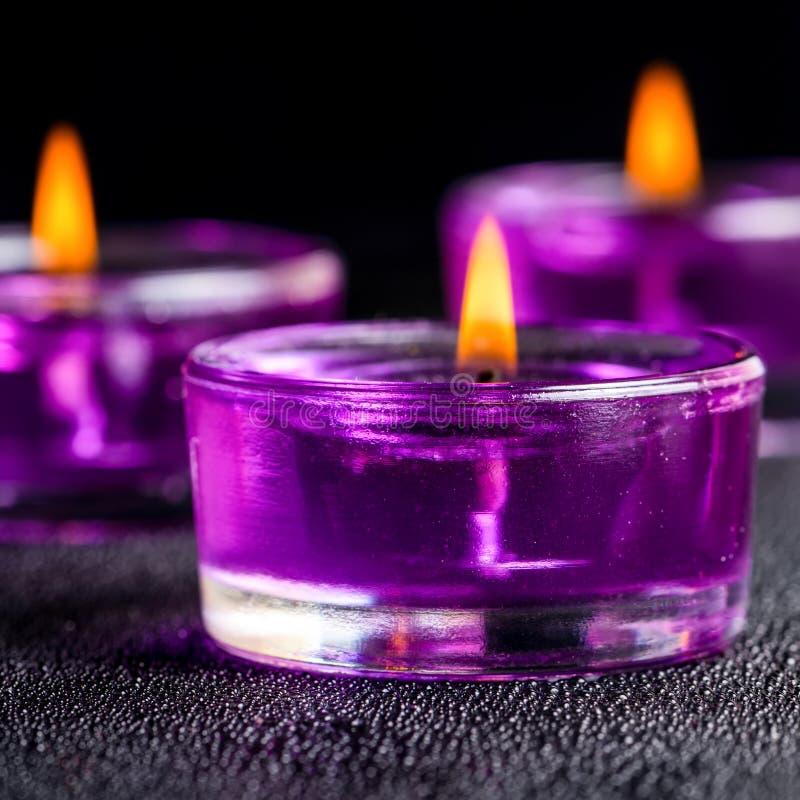 Tres velas púrpuras hermosas en un fondo negro con agua fotografía de archivo