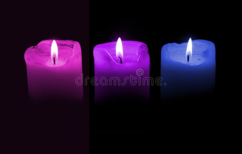 Tres velas, púrpuras y azules imagen de archivo