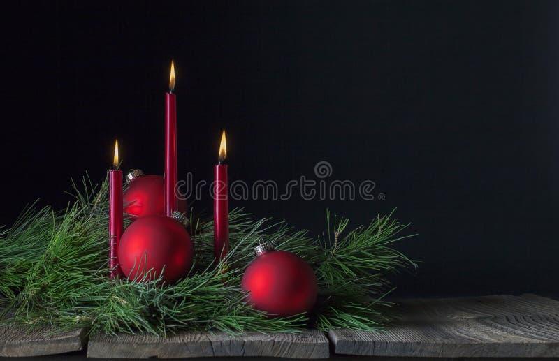 Tres velas rojas tres ornamentos de la Navidad foto de archivo libre de regalías