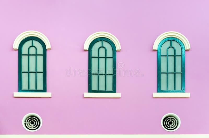 Tres ventanas arqueadas verdes en la pared rosada fotos de archivo