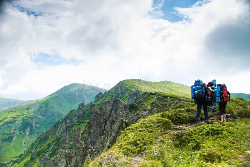 Tres viajeros en montañas fotos de archivo