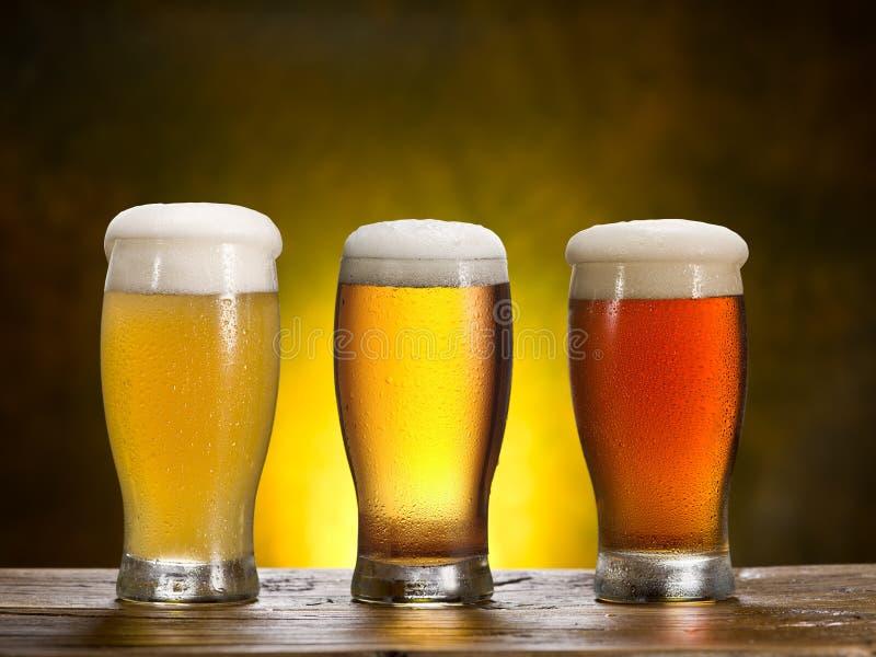 Tres vidrios de cerveza en la tabla de madera fotografía de archivo