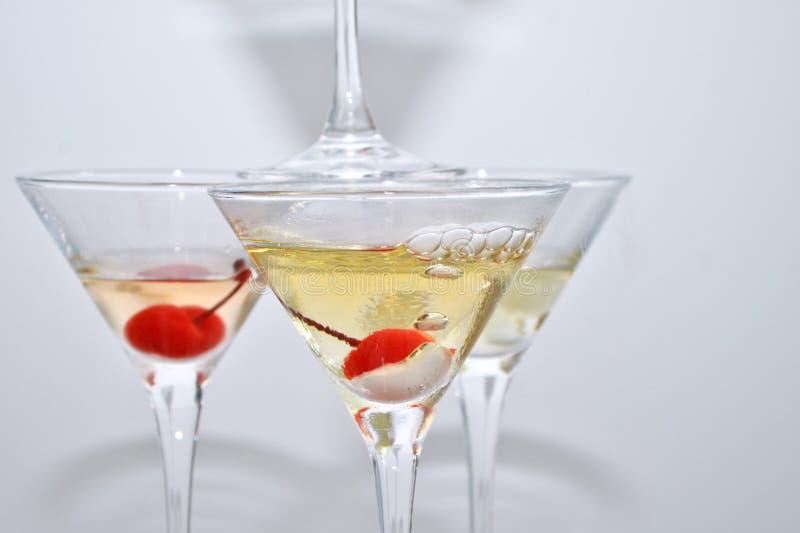 Tres vidrios de martini, con las cerezas y el nitrógeno líquido, creando el vapor, construido en la forma de una pirámide fotos de archivo libres de regalías