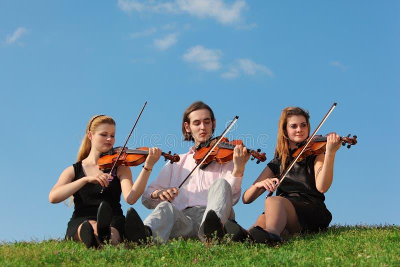 Tres violinistas se sientan y juegan en hierba contra el cielo imagen de archivo libre de regalías