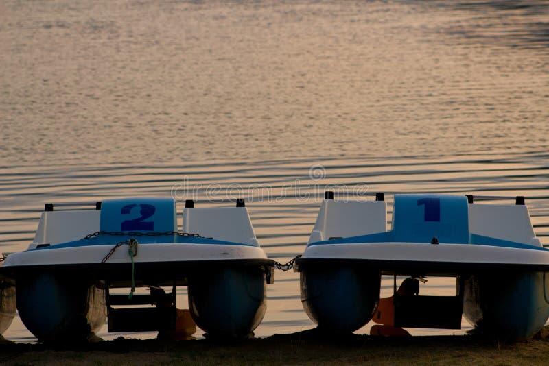 Tretboote parkten auf dem Ufer der Lipno-Verdammung bei Sonnenuntergang lizenzfreie stockfotos