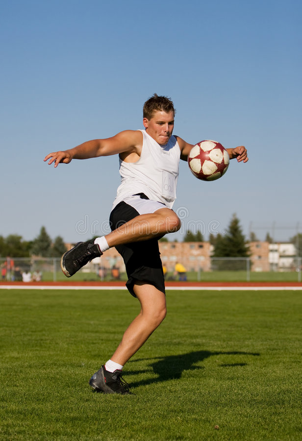 Treten einer Fußballkugel lizenzfreie stockbilder