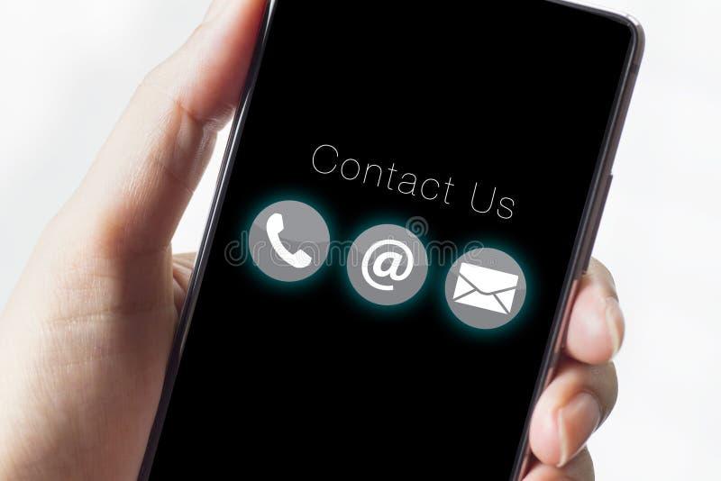 Treten Sie mit uns Ikonen auf Smartphone mit der Hand in Verbindung lizenzfreie stockbilder