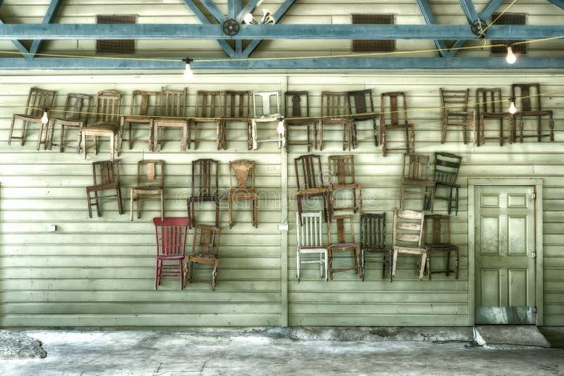 Trettio hängande stolar och en dörr arkivbild