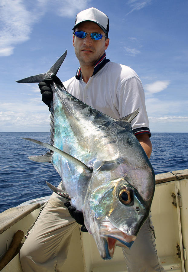 Trevally jack. Big game fishing. a fisherman holding a trevally jack royalty free stock photography