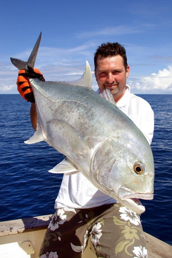 Trevally jack. Big game fishing. Happy fisherman holding a trevally jack royalty free stock photo
