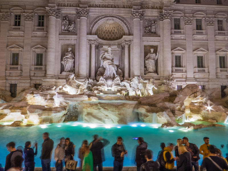 A kiss out of time. Trevi Fountain by night with long exposure. Everybody is moving, except a kissing couple posing for a selfie, creating a magical effect of