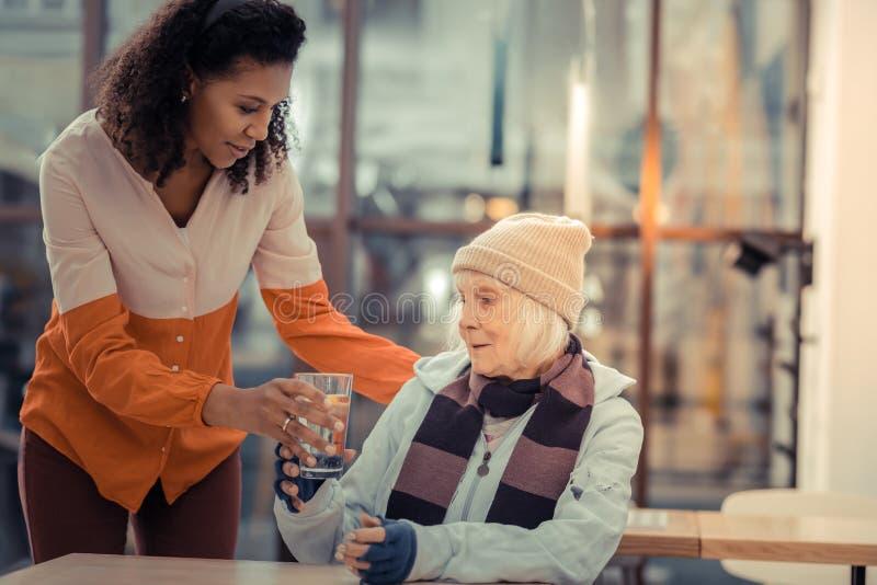 Trevlig äldre kvinna som tar ett exponeringsglas med vatten arkivbild