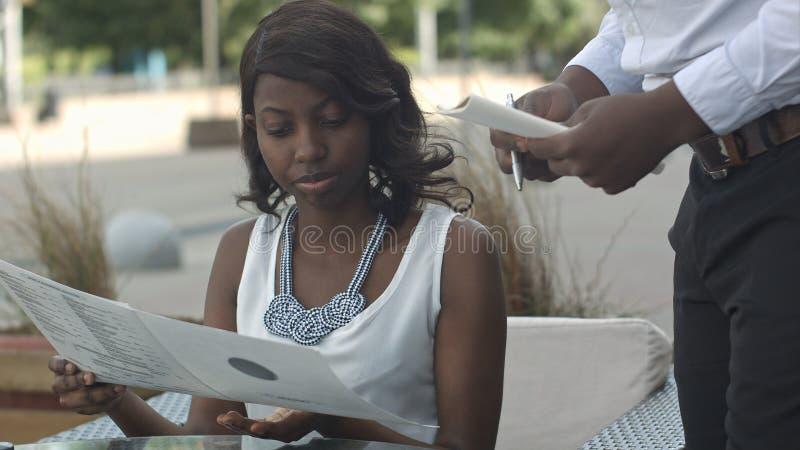 Trevlig afrikansk amerikanflicka med mörkt hår genom att använda smartphonen och ta beställning i utvändig restaurang royaltyfri bild