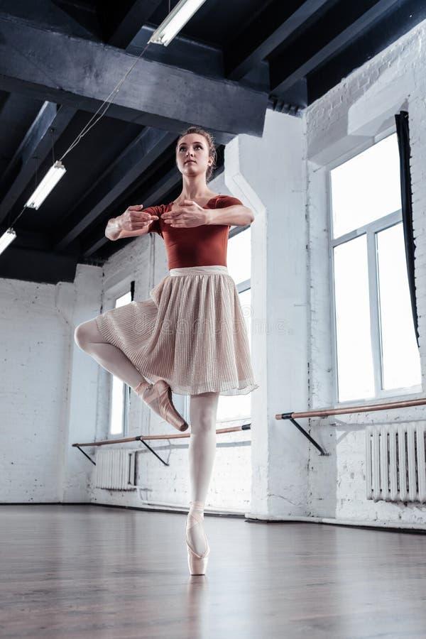 Trevlig allvarlig ballerina som förbereder sig att göra en piruett royaltyfri fotografi