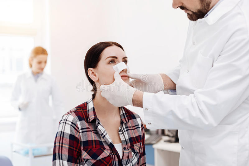 Trevlig allvarlig kvinna som har en medicinsk dressing på hennes näsa royaltyfria foton