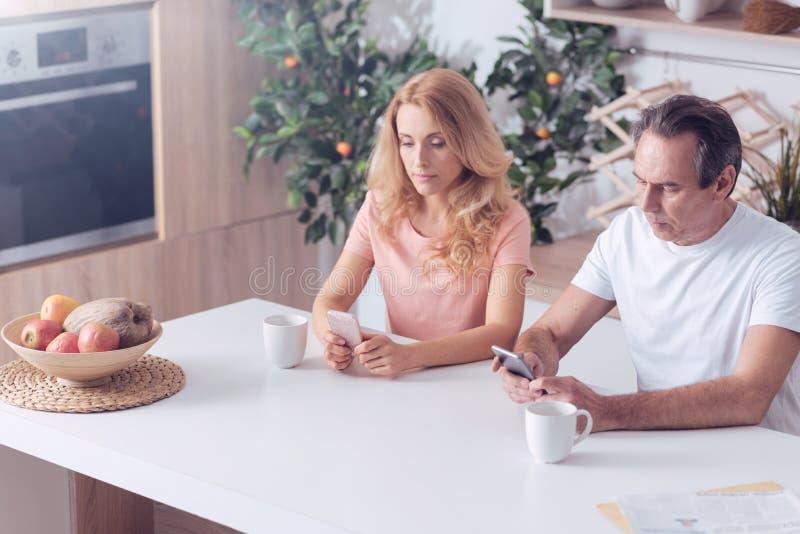 Trevlig allvarlig man och kvinna som använder deras smartphones royaltyfri foto